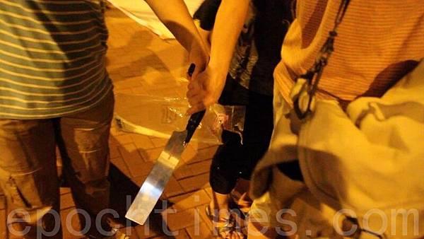 今年7月4日晚,青關會成員在落馬洲出動鋸刀,涉嫌恐嚇在場的法輪功學員和採訪記者,但現場的警察卻以沒有人受傷為由,只是登記在案,不作任何處理。(大紀元)