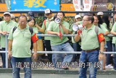 今年11月25日,聽命於梁振英的青關會頭目林國安(綠衣前左一)和楊江(綠衣前右一)身帶紅袖章,糾集徒眾,在路邊干擾法輪功學員舉辦的退黨遊行。楊江用高聲喇叭高叫污衊法輪功的口號。(新唐人電視台擷圖)