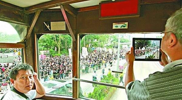 有市民不參加遊行,卻在電車上拍下這萬人空巷的一刻。李家皓攝