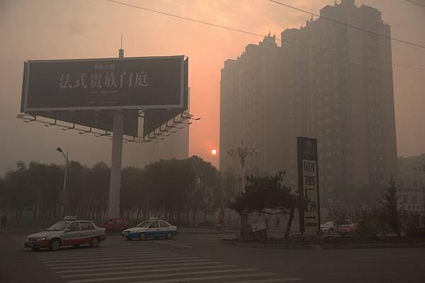 2013年10月22日,吉林省吉林市,市民戴著口罩在霧霾中出行。當日,吉林省吉林市霧霾天氣較前一天更重,能見度更低,車輛開燈緩行,中、小學停課一天。(大紀元資料室)