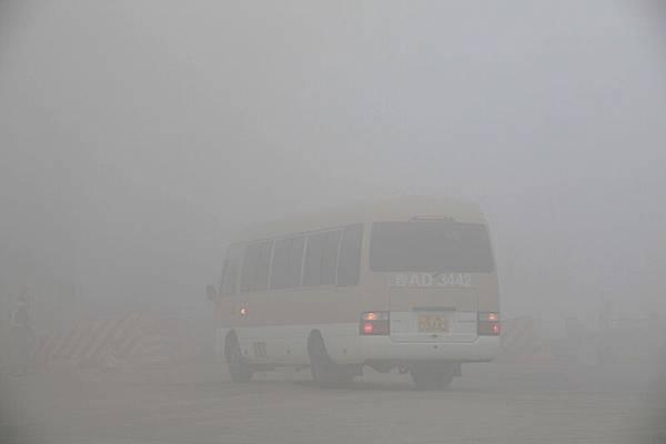 哈爾濱市部份路段能見度不足50米,車輛在霧霾中緩慢前行。(CHINA OUT AFP PHOTO)