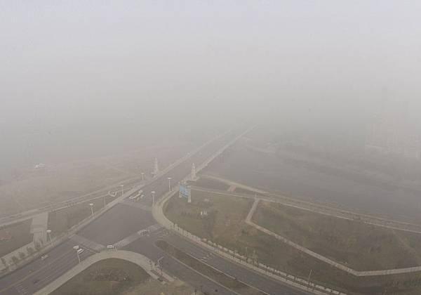 大陸東北地區連續數天籠罩在重度霧霾中,空氣5米之外看不清人,猶如世界末日來臨。圖為籠罩在一片令人窒息的霧霾之中的哈爾濱。(CHINA OUT AFP PHOTO)