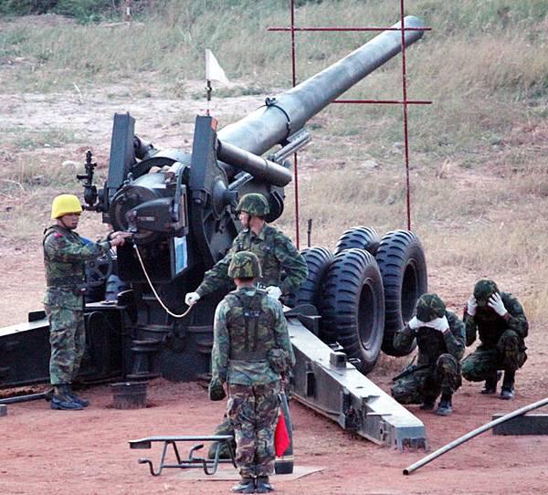 金門重砲實彈射擊演習23日清晨在金寧鄉后湖海邊舉行,圖為裝彈後安全士官(左)進行檢驗,確認安全後將進行擊發。(中央社