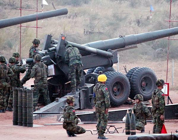 金門重砲實彈射擊演習23日清晨在金寧鄉后湖海邊舉行,圖為裝彈後安全士官(左)進行檢驗,確認安全後將進行擊發。(中央社)
