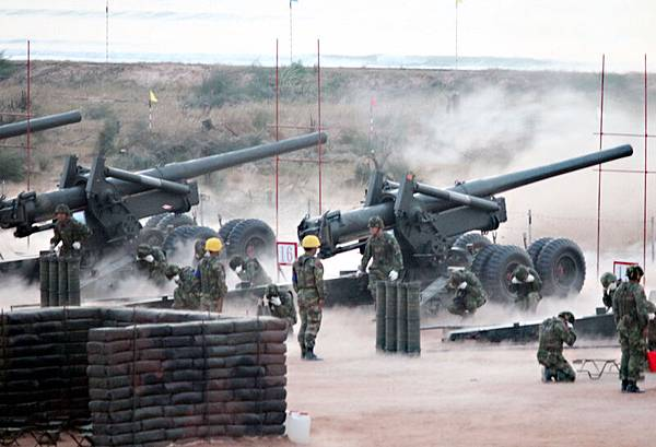 金門重砲實彈射擊演習23日清晨在金寧鄉后湖海邊舉行,圖為士兵進行砲彈填裝作業。(中央社)