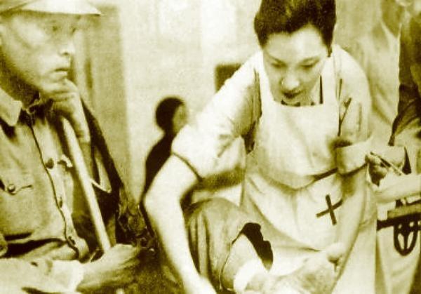 1938年宋美齡在戰區為抗日受傷戰士包紮傷口。(法新社)