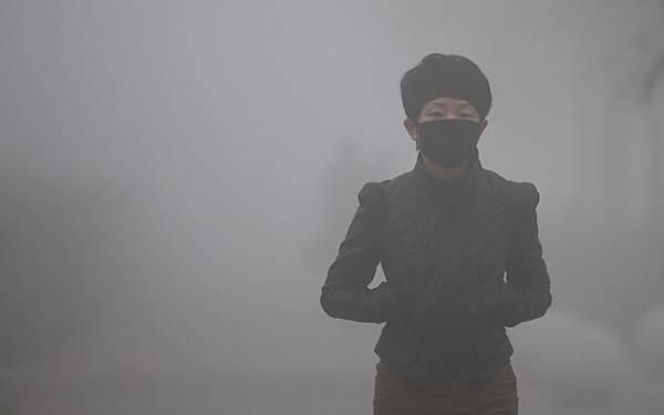 大陸霧霾籠罩全國,就連被稱空氣質量最好的海南三亞25日亦被霧霾籠罩。世衛組織的「大氣污染可致癌」的報告令中國民眾普遍恐慌。東北三省口罩已經全面脫銷。圖為,10月21日,長春霧霾嚴重,能見度很低,出午的人們都帶上口罩出行的。(ChinaFotoPress/Getty Images)