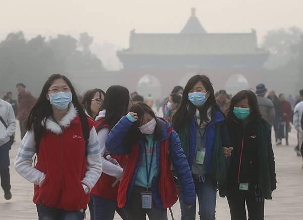 中國大陸28日再次遭遇大面積嚴重霧霾籠罩。圖為北京霧霾籠罩,市民戴口罩出門。(大紀元資料室)