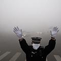 據港媒報導,籠罩中國的霧霾不只危害健康,對中共當局來說,霧霾也擾亂監控攝像頭,認為已危及國家安全。圖為,10月22日,哈爾賓霧霾嚴重,交警在路上指揮交通。(STR/AFP/Getty Images) (記者古清兒綜合報導)
