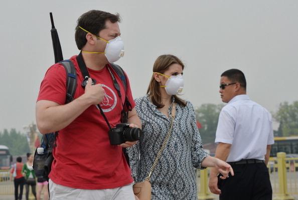 今年8月,兩位外國遊客走在北京天安門廣場上,右邊身後疑為便衣警察。 ( MARK RALSTON/AFP/Getty   Images)