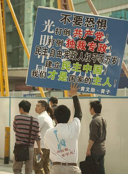 3月10日下午三點多,黃子在深圳的街頭遊行,打出「打倒共產黨!結束獨裁!建立民主中國」的牌子。(網絡圖片)