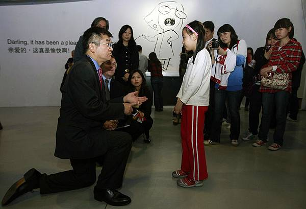 2011年10月13日,美國駐華大使駱家輝(中)和翻譯(左)單膝「跪」在楊芷湄(右)面前,講了十幾分鐘話。(大紀元資料室)