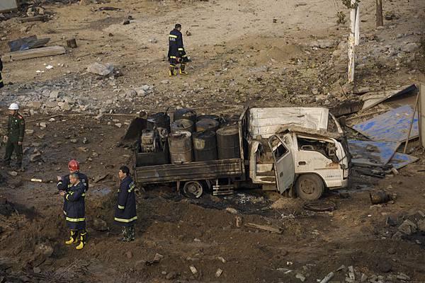 11月22日凌晨2時許,山東省青島市中石化黃濰輸油管線一輸油管道發生原油洩漏。上午10時許,在搶  修的過程中,管道破裂處起火引發大爆炸,升起黑色蘑菇雲。圖為,爆炸現場,汽車被炸飛。  (STR/AFP/Getty Images)
