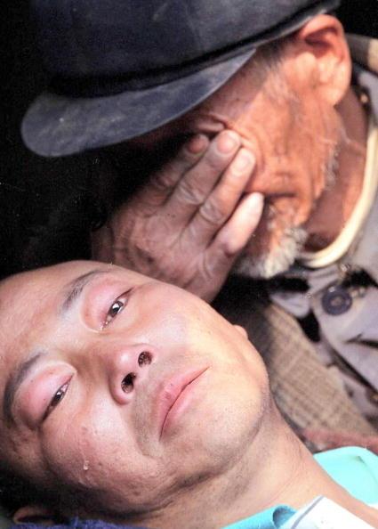 2009年愛滋病是造成最多中國人死亡的傳染病。 圖為一位父親抱著因賣血而感染愛滋病的兒子哭泣。  (Getty Images)(Stringer: STR / 2004 AFP)
