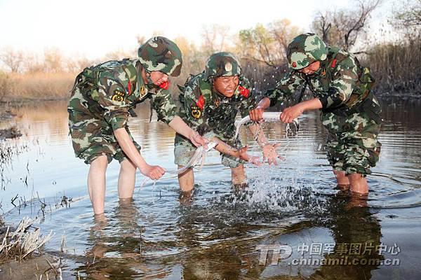在《解放軍報》報導中,以士兵在新疆淡水河裡抓帶魚,來展示軍力。(網絡圖片)