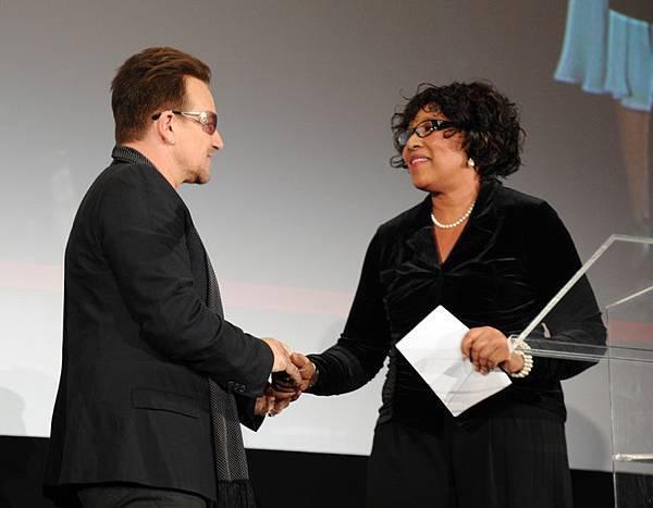 2003年11月25日,U2樂隊主唱波諾(左)與《時尚》雜誌主編安娜‧溫特在紐約共同主持影片《曼德拉:漫漫自由路》特別放映會時,現任南非駐阿根廷大使的曼德拉之女澤娜妮‧曼德拉(右)現身講話。(Bryan Bedder/Getty Images for The Weinstein Company)