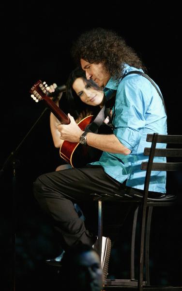 2003年11月29日,英國皇后樂隊吉他手布萊恩‧梅與可兒家族樂隊主唱安德莉亞‧可兒在開普敦46664艾滋病慈善音樂會上同台表演。(Getty Images)