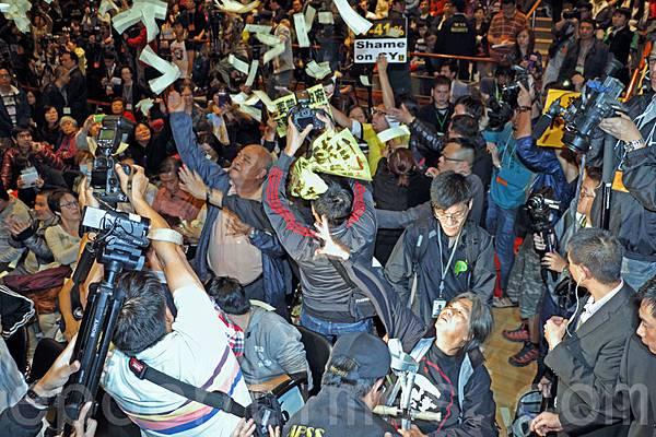 梁振英12月8日下午2時半到大角咀出席第三場地區諮詢會,多個民間團體到場示威抗議,斥責中共打  壓民主普選,社民連和人民力量成員現場撒冥紙,要求民望創紀錄負數的梁振英下台,之後被保安趕  離場。(潘在殊/大紀元)