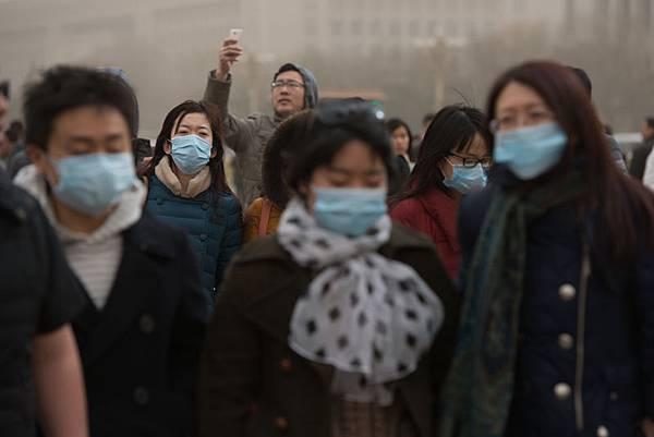 世界衛生組織(WHO)近期已經表明空氣污染可以導致癌症,而許多專家也表示陰霾會危及心臟和心  血管的健康。圖為北京民眾戴口罩防霾。(AFP PHOTO / Ed Jones)