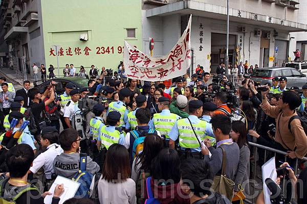梁賊振英到觀塘出席活動,遇到一批示威者在場外抗議,警方以鐵馬和人牆攔阻。(潘在殊/大紀元  )