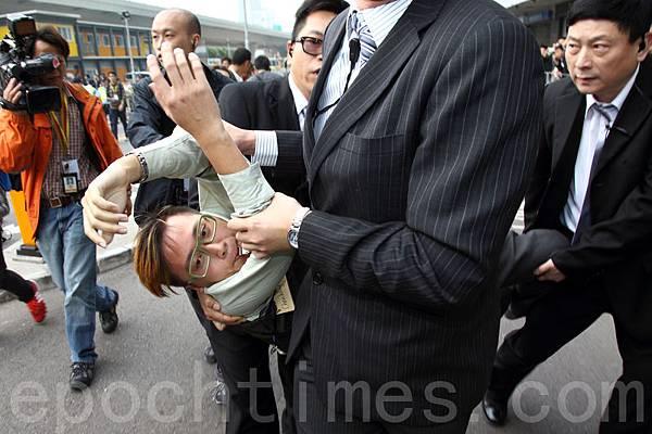 在會場內舉牌抗議的示威者,遭多名穿西裝保安強行抬離現場。(潘在殊/大紀元)