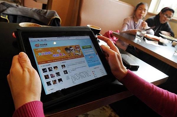 蘋果公司最近再度順從中共當局的要求,從中國App Store中移除手機翻牆軟件「自由微博」  (FreeWeibo)。圖為一名北京女子在使用新浪微博。(Photo by MARK RALSTON / AFP)