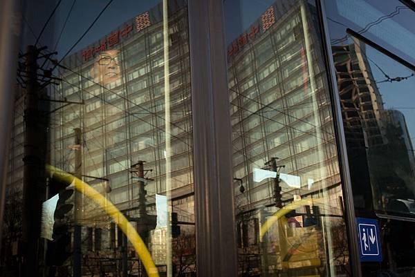 根據中共財政部數據估算,12月公共財政有近2.5萬億資金可供花費,接近於前三個月花費總和,每週平均  花費5千億元。圖為,2013年11月29日,北京一男子透過公交車窗向外張望。(ED JONES/AFP/Getty Images)