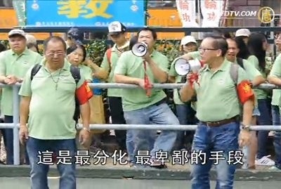 中共610辦公室主任和公安部副部長李東生被調查,中共610系統在香港成立的分支機構——香港青年關愛  協會(青關會),也面臨解散。圖為去年11月25日,聽命於梁振英的青關會頭目林國安(綠衣前左一)和  楊江(綠衣前右一)身帶紅袖章,糾集徒眾,在路邊干擾法輪功學員舉辦的退黨遊行。(新唐人電視台擷  圖)