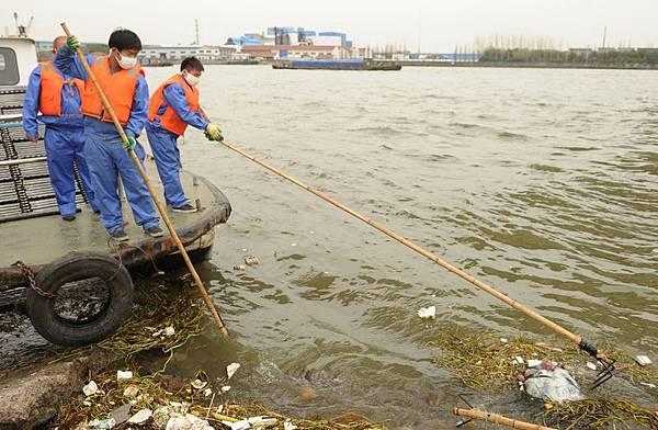 時至2013年年底,但是3月的「黃浦江死豬」、5月的「鎘大米」,還有杭州「5•19強姦致死案」至今沒有結果,成為今年的「爛尾新聞」。圖為,黃浦江死豬事件,環衛工人在打撈惡死豬。(PETER PARKS/AFP/Getty Images)