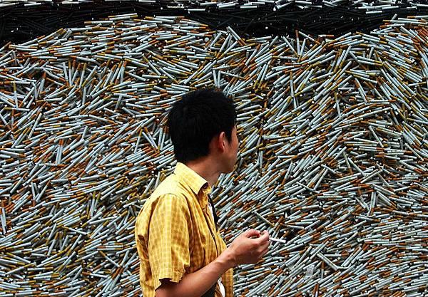 圖為一名中國吸菸者經過堆積如山的香菸廣告前,想到一生中吸了這麼多的菸,危害健康的惡果讓人不寒  而慄。(AFP)