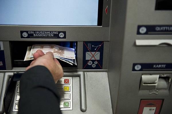 今年稍早,歐洲黑客利用U盤將惡意軟件植入自動提款機,以竊取鈔票。圖為德國民眾在使用提款機。(Photo by JOHN MACDOUGALL / AFP)