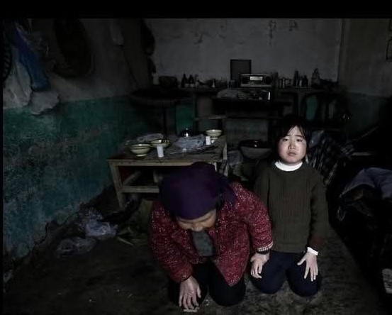 河南省舞鋼市洪河邊的劉家灣村,13歲的楊逍,2008年11月得了怪病。在學校、村民們的捐款幫助下得救了,老奶奶看到老村長來看望孫女就拉著孫女的手跪在地上謝恩。2009年4月19日(網絡圖片)