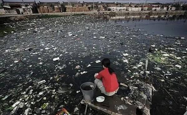 廣東省貴嶼鎮河流、水塘都已被污染,村民們只好在被嚴重污染的水塘裡洗滌。2005年11月25日 (網絡圖片)