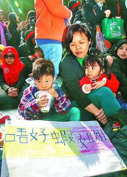 ■蔡氏一家昨參與遊行,小兒子親手寫「唔好蝦姐姐」橫額支持外傭。翁鈺輝攝