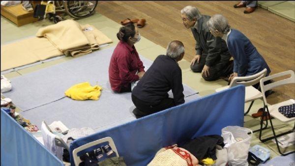 圖為日本天皇夫婦見災民。(網絡圖片)