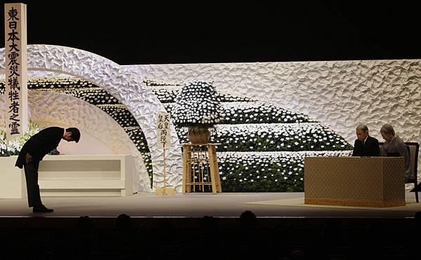 2013年3月11日在在東京的全國追悼會上,日本首相安倍晉三(Shinzo Abe)(左)向(右二)明仁天皇( Emperor   Akihito)和美智子皇后( Empress Michiko)深深的鞠躬,全體的日本人都為2011年地震和海嘯的受害者低頭默哀。