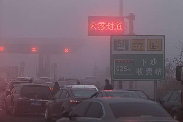日漸嚴重的陰霾和H7N9禽流感成為大陸民眾過年期間的熱點話題,令民眾在喜慶的節日愁雲瀰漫。圖為,2014年1月31日,杭州市高速入口處車輛在排隊等候上高速。早上8點之間杭州市內及周邊道路能見度不足200米。(資料室)
