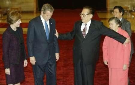 布殊訪問北京,江本該將王冶平介紹給布殊夫人,誰知反而一把把她攔在後面,另一隻手推開布殊,讓準備上前去與布殊夫人握手的王冶平臉色大變。布殊緊皺眉頭,低頭思索,表情痛苦。(網絡圖片)