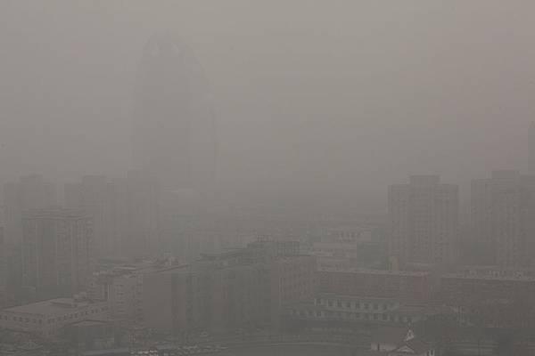 中國大陸多地陰霾持續拉警報。嗆人的陰霾讓30多個城市成為揮之不去的陰影。圖為,2014年2月24日,北京人民日報大樓「消失」在陰霾中。(大紀元資料室)