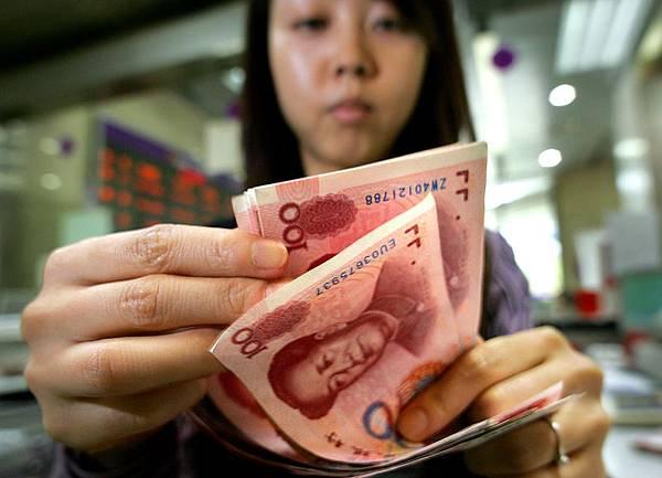 人民幣匯率連連下跌。一週來,人民幣即期匯率跌幅超1%。去年2013年全年升值2.9%。圖為北京一家銀行行員在點算人民幣百元大鈔。(AFP PHOTO / Frederic J. BROWN / FILES)
