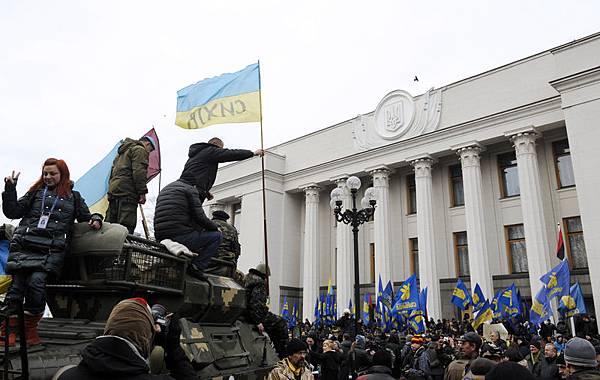 當地時間2月27日,幾十個武裝份子持槍佔領了烏克蘭南部克里米亞地區政府辦公大樓和議會,掛出俄羅斯國旗,挑釁烏克蘭的新領導人。為此,烏克蘭臨時政府向俄羅斯發出警告。圖為27日基輔的議會大樓前,人們舉出烏克蘭國旗。( AFP PHOTO / YURIY DYACHYSHYN)