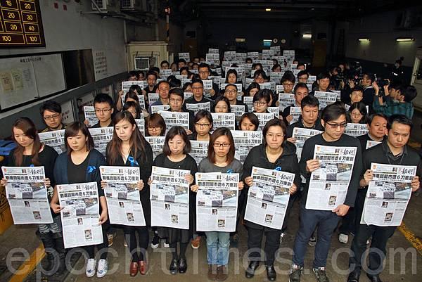 超過100名明報員工身穿黑衣,配戴藍絲帶,聚集在柴灣的公司門外,他們手持當天報導劉進圖遇襲的報紙默站抗  議,指明報報頭轉為黑色,是新聞界最黑暗的事。(潘在殊/大紀元)