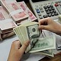 目前,中國經濟危如累卵。人民幣兌美元貶值成為中共兩會最熱門的話題之一,有香港專家認為,未來兩年人民幣還會繼續貶值。(STR/AFP/Getty Images)
