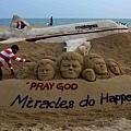 2014年3月9日,印度沙雕藝術家Sudersan Pattnaik在普里海灘製作沙雕作品,為馬航失聯航班乘客祈福。(ASIT KUMAR/AFP)