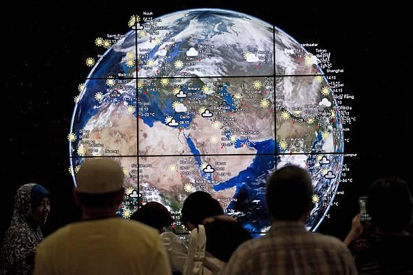 3月15日,馬來西亞總理納吉布終於承認,馬航失聯是遭劫持。2014年3月16日,乘客在在吉隆坡國際機場觀看一個「數碼地球」。(MOHD RASFAN/AFP/Getty Images)