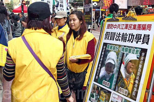 青關會成員穿上黃衣服冒充法輪功學員,派發污衊法輪功的單張,欺騙市民,做法卑劣。(潘在殊/大紀元)