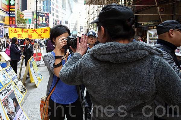 3月23日,路透社女記者到場採訪青關會侵擾法輪功真相點,遭青關會惡徒阻擋採訪和粗言辱罵,要警員在場保護。(潘在殊/大紀元)