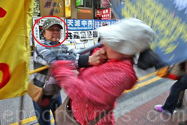 3月22日星期六,身穿便服的青關會女成員陶桂香(紅圈中)揮拳毆打法輪功學員(右),並把她推倒在地,其後再作勢  倒地假裝昏倒,試圖栽贓法輪功學員。(潘在殊/大紀元)