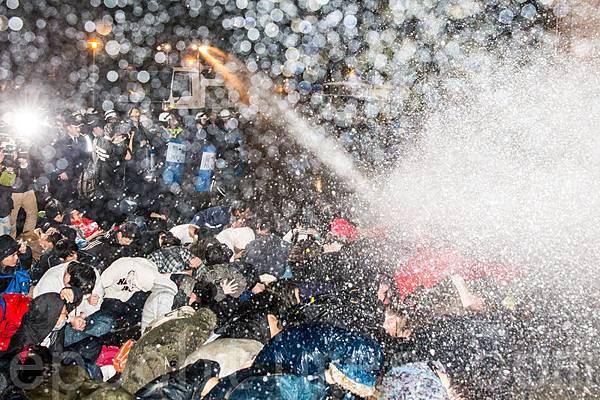 反服貿學生23日晚間攻占行政院,警方24日凌晨以高壓水柱、抬人強制驅離。(陳柏州/大紀元)