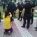 兒子被特警暴打,一旁的媽媽跪地求情。(網絡圖片)